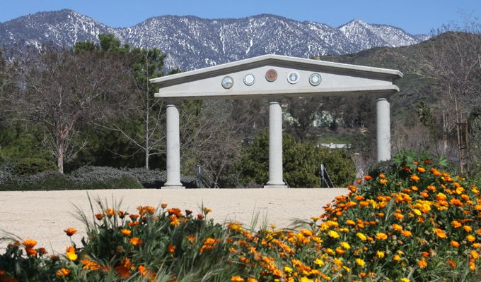 The monument in Flag Hill Park in Yucaipa with the San Bernardino Mountains